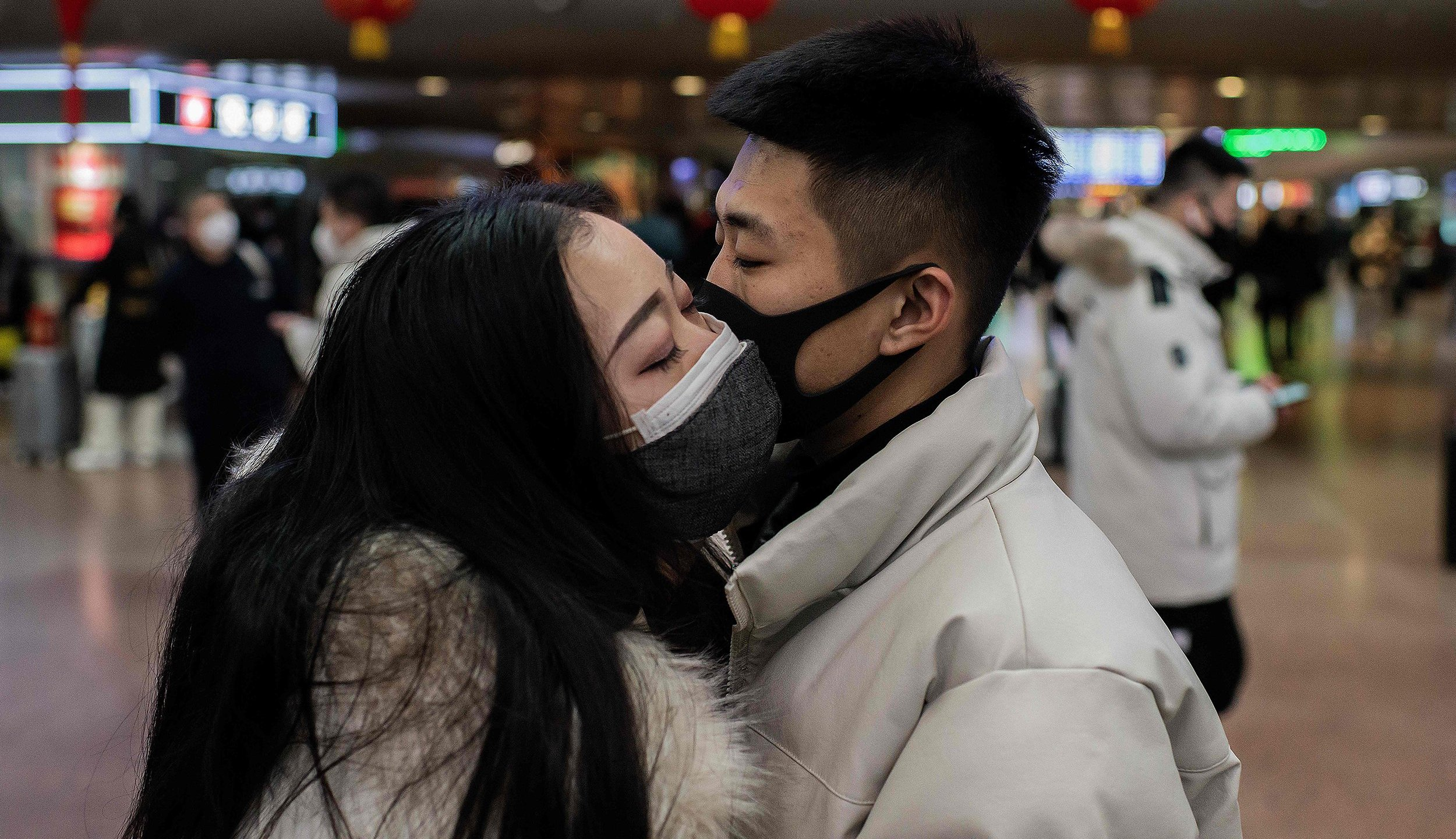 TOPSHOT - A couple, wearing protective masks, kisses goodbye as they travel for the Lunar New Year holidays, at Beijing West Railway Station in Beijing on January 24, 2020. - Chinese authorities rapidly expanded a mammoth quarantine effort aimed at containing a deadly contagion on January 24 to 13 cities and a staggering 41 million people, as nervous residents were checked for fevers and the death toll climbed to 26.