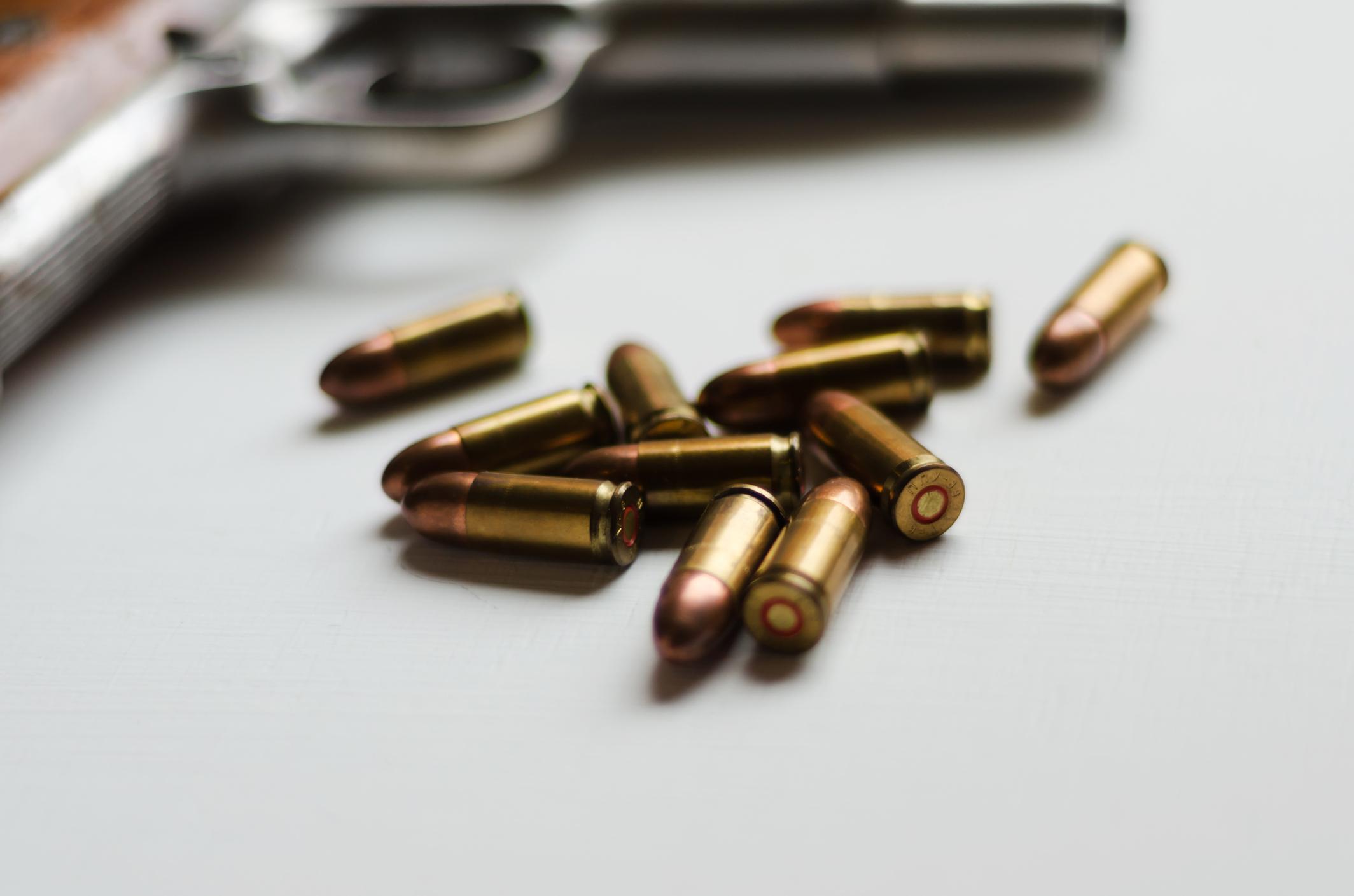 A handgun with ammunition on white background