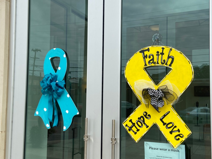 Athens City Hall doors display a teal ribbon for gynecologic cancer and a gold ribbon for childhood cancer.
